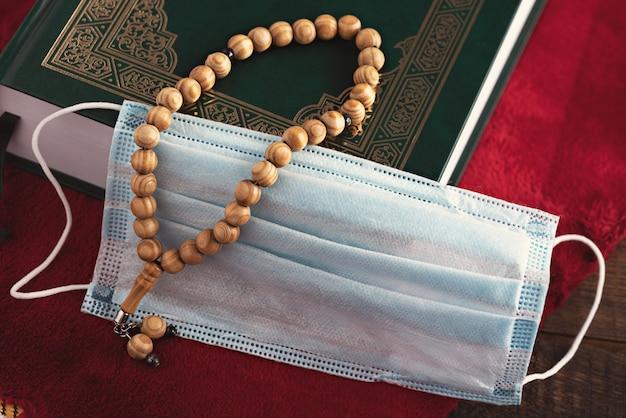 Close-up rosario in legno perline, corano, mascherina medica sul tappetino da preghiera rosso, concetto di ramadan, quarantena