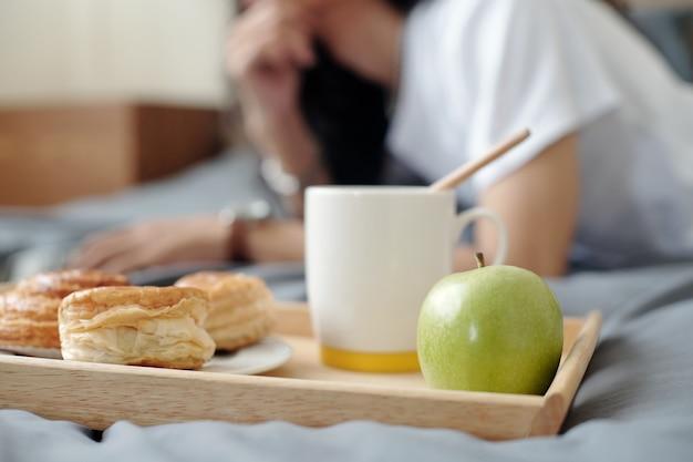 Primo piano del vassoio di legno con colazione come mela, tazza da caffè e panini sul letto dove l'uomo lavora con il laptop