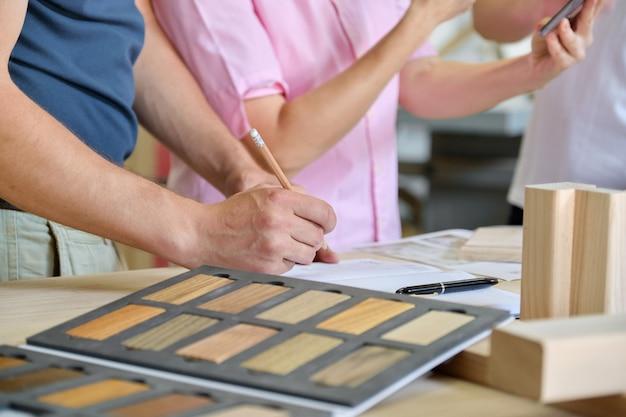 Chiuda sul lavoro nel laboratorio di falegnameria, mani di lavoratori, tavolozza di mobili in legno