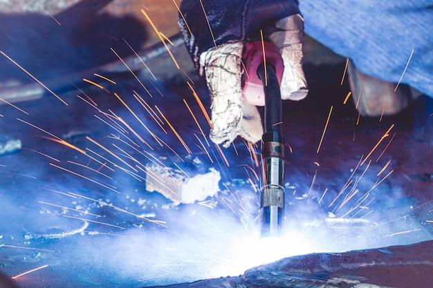 Saldatura a gas inerte (mig) di metallo da lavoro ravvicinato o saldatura di acciai al carbonio su piastra metallica alla struttura. il processo può essere semiautomatico o automatico.