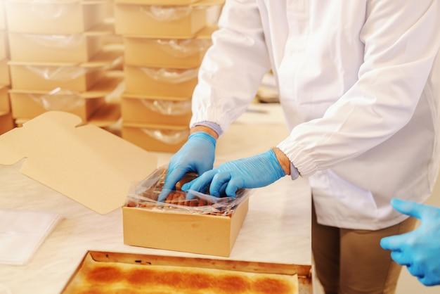 Chiuda in su del lavoratore che imballa biscotti deliziosi nella casella. interno della fabbrica alimentare.