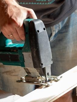Primo piano di un lavoratore che sega una tavola di legno con un seghetto alternativo elettrico