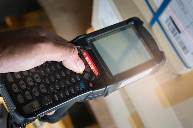 Scanner di codici a barre di scansione dell'operaio del primo piano con la spedizione del carico