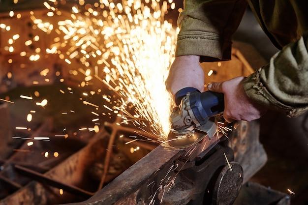 Primo piano del lavoratore che utilizza la smerigliatrice per macinare il metallo nell'impianto