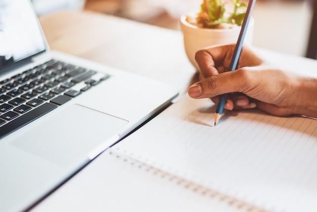 Chiuda su della mano della donna lavoratrice facendo uso del computer portatile e scrivendo la lettera sulla carta del taccuino nella scrivania. stili di vita commerciali e delle persone. investimenti finanziari ed economici.