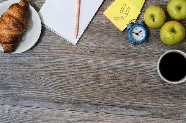 Primo piano del posto di lavoro: tazza di caffè, mele, piatto con croissant, blocco note e matita, sveglia e tavolo