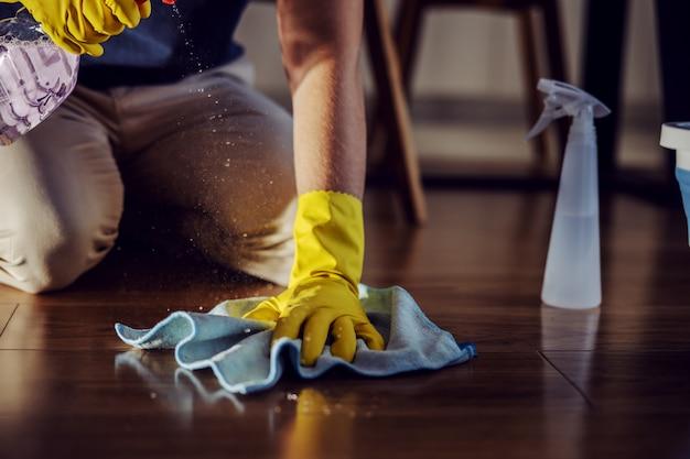 Close up degno uomo inginocchiato, spruzzare detergente e pulire il parquet a casa.