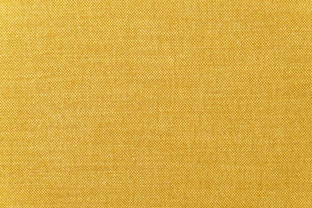 Trama della superficie del tessuto senape gialla o dorata ravvicinata per lo sfondo