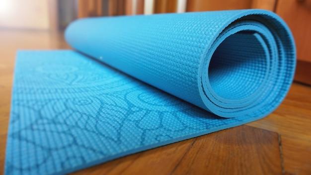 Primo piano di yoga, tappetino fitness a casa in un rotolo. puntelli e accessori per lo yoga, tappetino turchese acqua. concetto di stile di vita sano
