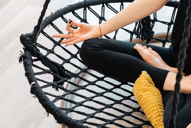 Chiuda in su della ragazza di yoga che si siede in asana del loto sull'amaca durante la lezione di yoga, vista ritagliata