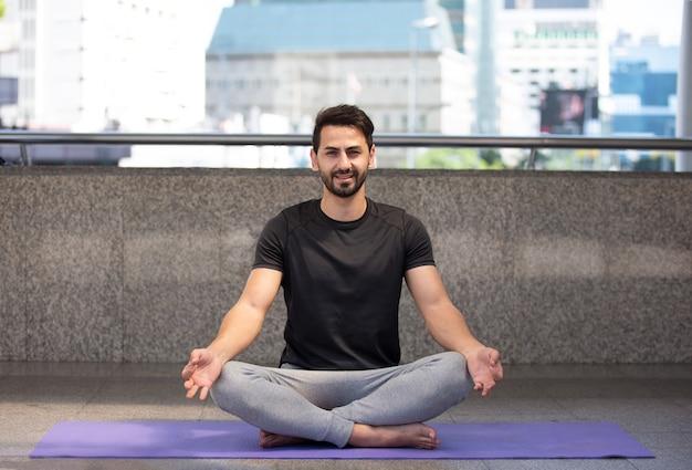 Primo piano di yoga uomo seduto in lotus asana
