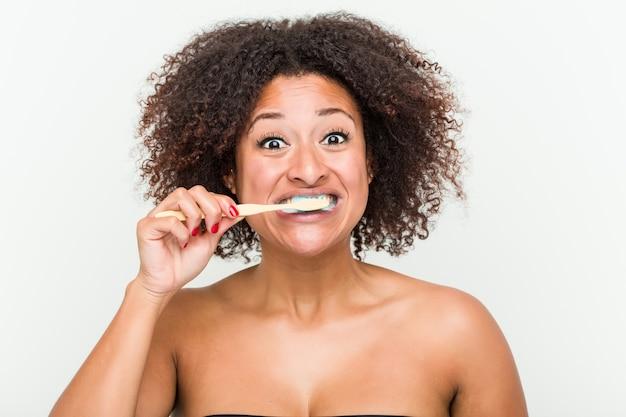 Primo piano di una giovane donna afro-americana lavarsi i denti con uno spazzolino da denti