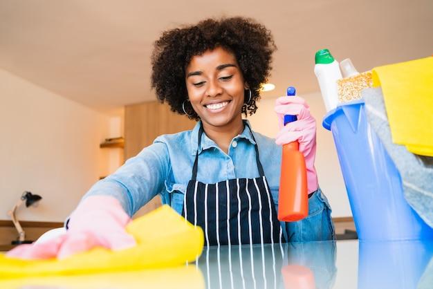 Chiuda in su della giovane donna afro pulizia nella nuova casa. concetto di pulizia e pulizia.