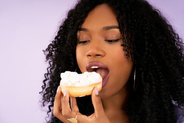 Primo piano di una giovane donna afro che mangia una ciambella mentre si sta in piedi su uno sfondo isolato. dolce e concetto di cibo.
