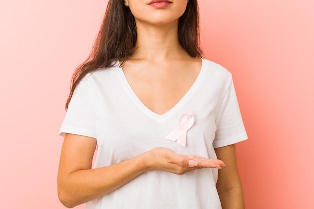 Primo piano di una giovane donna araba con un fiocco rosa. concetto di lotta contro il cancro.