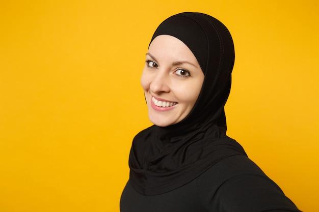 Chiuda sulla giovane donna musulmana araba in abiti neri hijab facendo selfie girato sul telefono cellulare isolato sul ritratto di parete gialla. concetto di stile di vita religioso della gente.