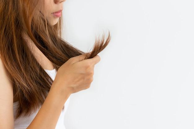 Close up della giovane ragazza asiatica guardando i suoi capelli danneggiati sul muro bianco con copia spazio