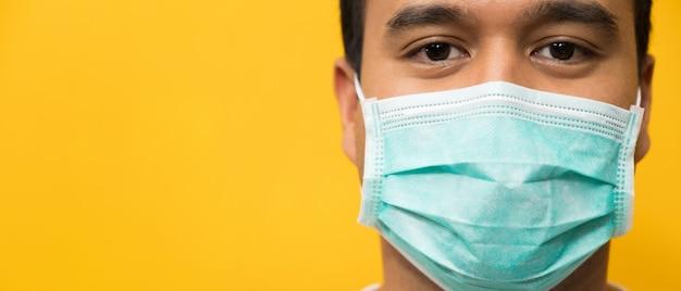 Chiuda sulla maschera di protezione d'uso del giovane uomo asiatico contro il coronavirus su giallo