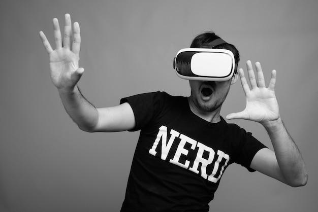 Primo piano di giovane uomo nerd asiatico utilizzando le cuffie da realtà virtuale