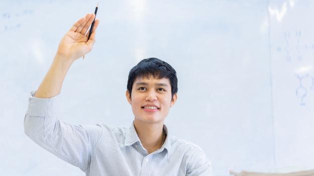 Chiuda sul giovane uomo asiatico dello studente universitario alzi la mano per chiedere all'insegnante del progetto o dell'esame in aula per l'istruzione e il concetto della gente