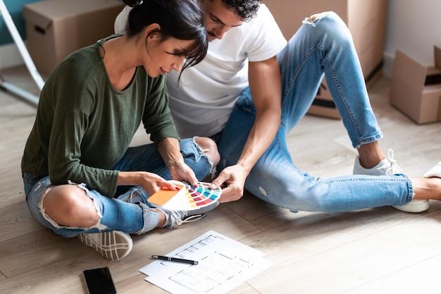 Primo piano di una giovane coppia attraente che sceglie i colori in una tavolozza di colori per dipingere le pareti dell'appartamento mentre è seduto sul pavimento.