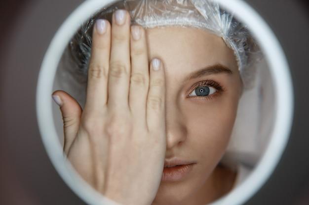 Chiuda sulla giovane donna attraente che si trova e che sembra diritta. si copre il viso con la mano. sguardo serio del cliente attraverso il foro di luce.