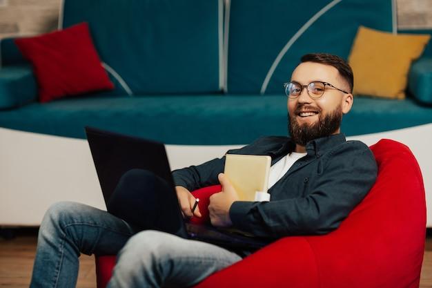 Chiuda in su del giovane uomo barbuto con gli occhiali che lavora al computer portatile in soggiorno. lui sorride nella telecamera.