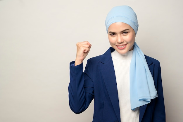 Una stretta di giovane bella imprenditrice musulmana con hijab isolato su sfondo bianco studio