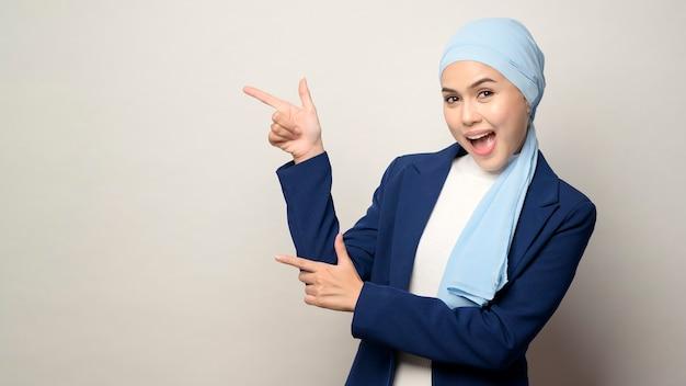 Un primo piano di giovane bella imprenditrice musulmana con hijab isolato sul muro bianco