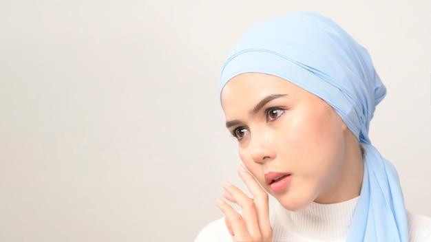 Una chiusura di giovane bella donna musulmana con hijab isolato su bianco, concetto di cura della pelle di bellezza musulmana.