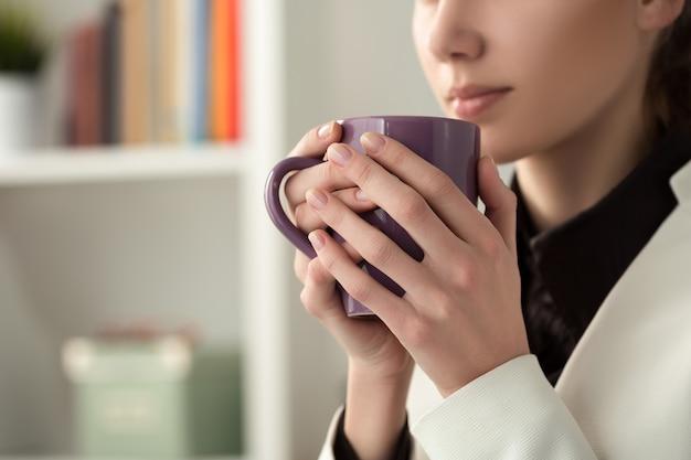 Primo piano di giovane bella donna che beve il tè