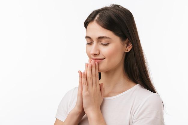 Primo piano di una giovane bella donna isolata, pregando