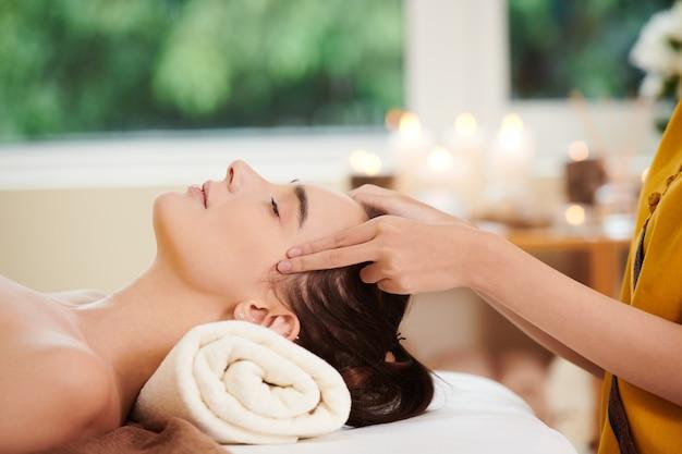 Primo piano di giovane bella donna che si rilassa durante il massaggio nel salone della stazione termale