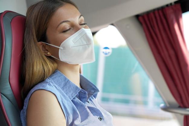 Primo piano di una giovane bella donna con maschera medica ffp2 kn95 che dorme seduta in autobus. passeggero dell'autobus che viaggia in sicurezza seduto su un sedile e dorme.