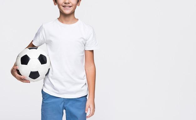 Giovane ragazzo del primo piano con la sfera di calcio
