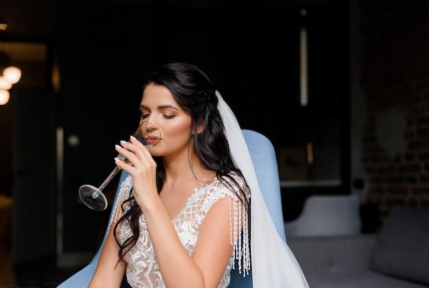 Primo piano di una giovane sposa bruna seduta su una croce e bevendo champagne in una stanza d'albergo