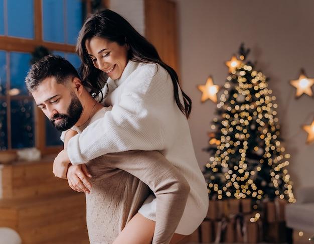 Primo piano di una giovane bruna saltata sulla schiena del suo ragazzo e sorride sullo sfondo dell'albero di natale