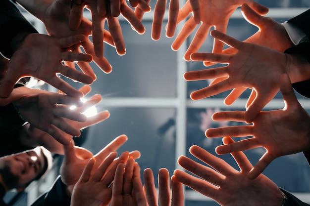 Avvicinamento. giovane squadra di affari in piedi in cerchio. concetto di lavoro di squadra.