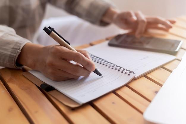 Chiuda sulle mani della giovane donna di affari con la penna che scrive note su dirigente femminile di carta che si siede alla tavola a casa ufficio