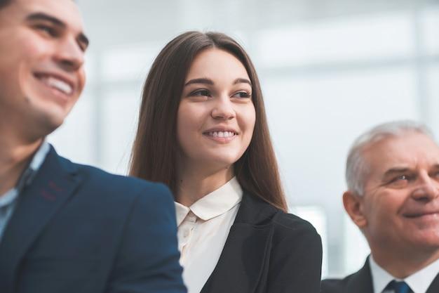 Avvicinamento. giovane donna d'affari in piedi con i suoi colleghi senior. il concetto di lavoro di squadra