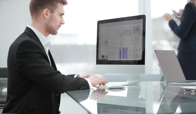 Primo piano.giovane uomo d'affari che lavora con grafici finanziari.foto con spazio di copia