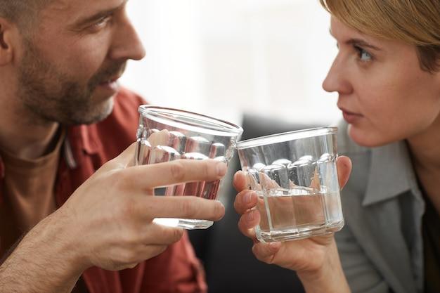 Primo piano di giovani coppie che esaminano e che tostano con i vetri delle bevande alcoliche