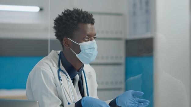 Primo piano di un giovane medico che parla con il paziente dell'assistenza sanitaria