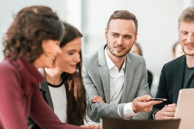 Avvicinamento. giovani dipendenti che discutono di problemi in una riunione di gruppo.