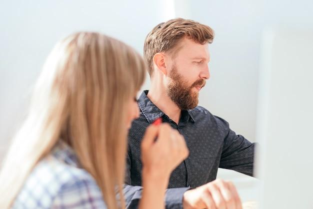 Primo piano i giovani dipendenti guardano la videoconferenza sul posto di lavoro