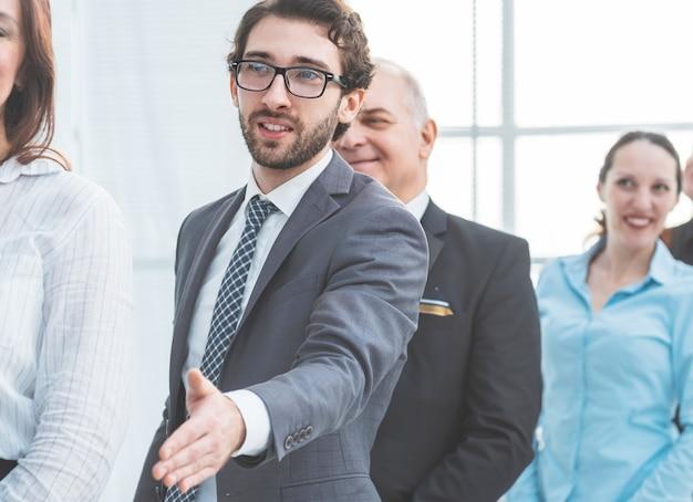 Avvicinamento. giovane imprenditore tendendo la mano per una stretta di mano. uomini d'affari