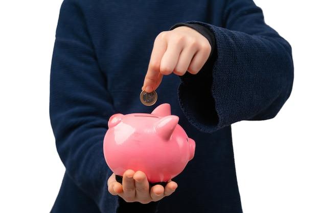 Primo piano di giovane imprenditore inserendo moneta nel salvadanaio
