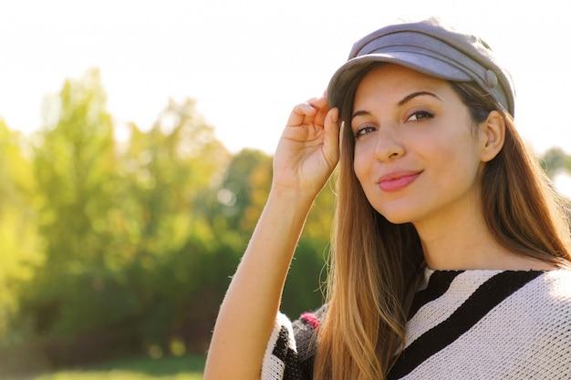 Primo piano di moda giovane donna con cappello nel parco sulla stagione autunnale. guardando la fotocamera.