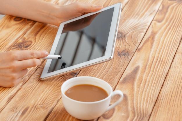 Primo piano di giovani mani femminili che tengono compressa digitale e che bevono il macchiato di mattina.
