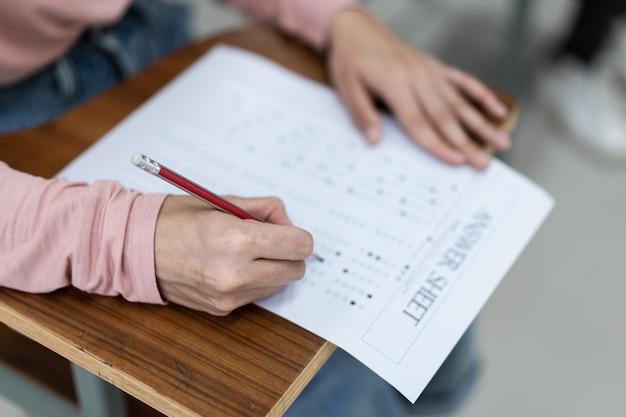 Primo piano di giovani studentesse universitarie si concentrano sul fare l'esame in classe. una studentessa scrive la risposta degli esami sul foglio delle risposte in classe.